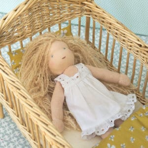Bergamote habillée avec la chemise de nuit, installée dans son lit en osier avec la literie Farandole
