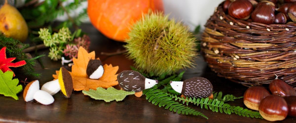 composition de table d'automne avec feuilles, champignons et hérissons en feutrine accompagnés d'éléments de la nature